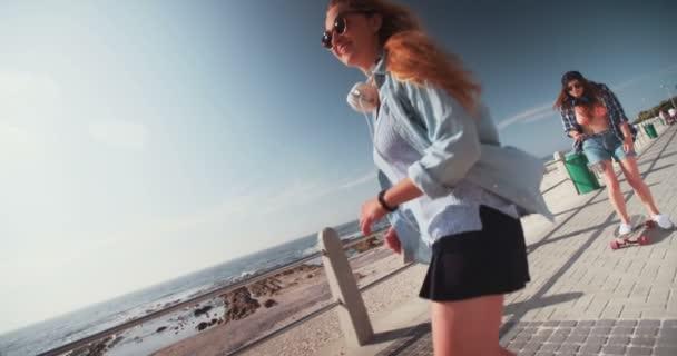 dívky na koních skateboardy podél chodníku na pláži