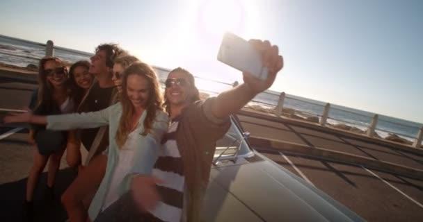přátel grimasy, brát selfie na pláži
