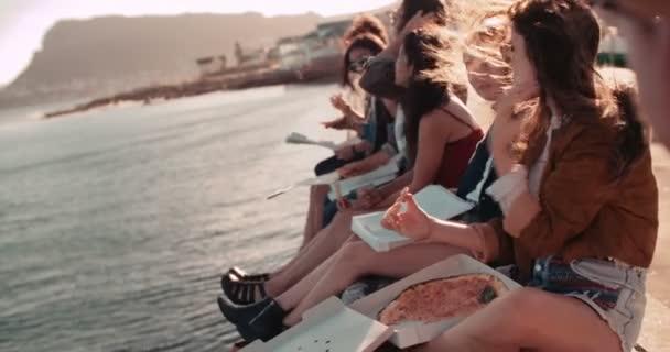 teenager přátel jíst pizzu na lavici obžalovaných