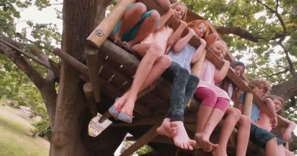 Děti sedí na okraji treehouse stromu
