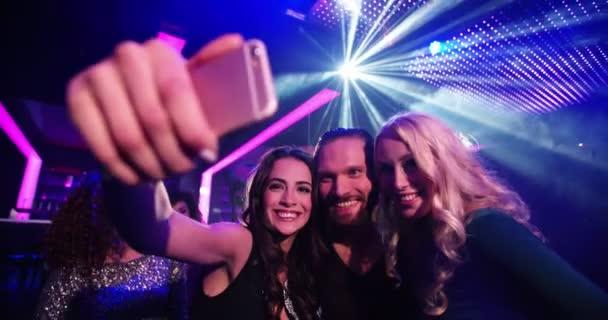 Mladé party lidí, kteří selfie na parketu klubu