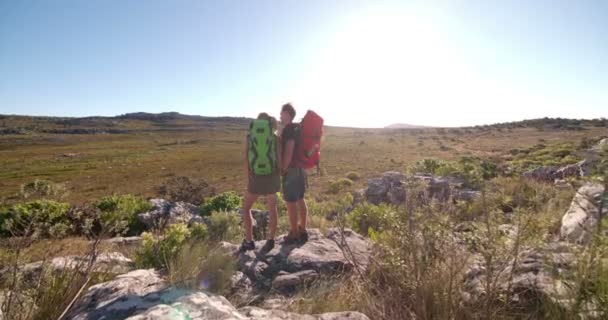 Couple hiking together with backpacks in rocky landscape