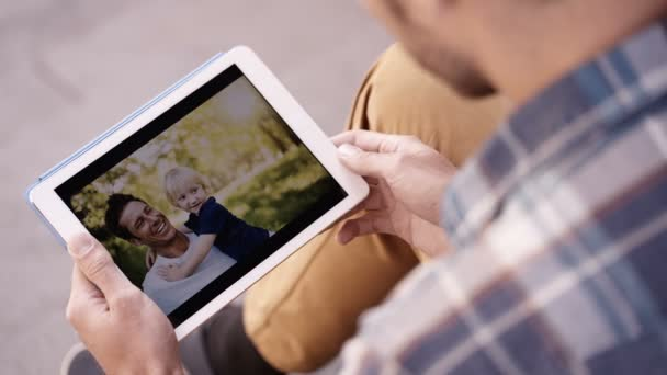 Man looks at photos on tablet