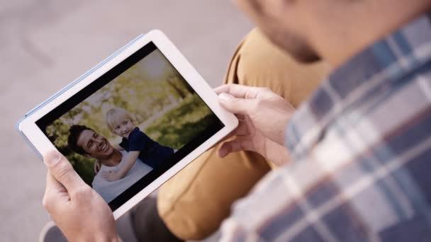 Člověk se dívá na fotky na tabletu