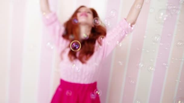 Krásná rusovlasá dívka mezi mýdlové bubliny