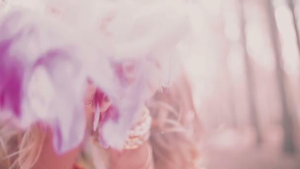 Boho girl blowing pink feathers