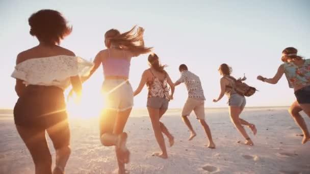 Mladí přátelé, běží na pláži při západu slunce