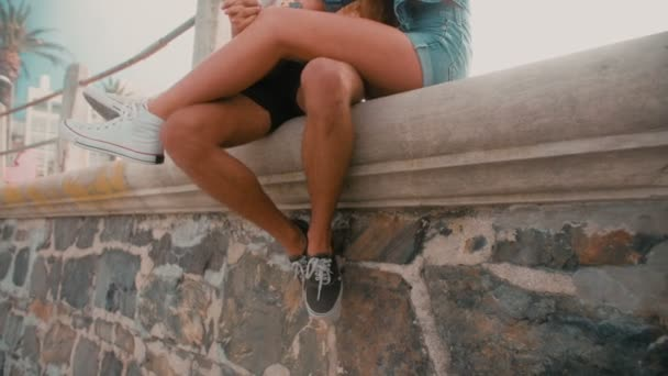Hipster couple sitting on wall