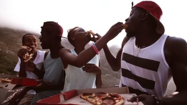 Přátel spolu smát při sdílení pizza