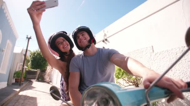 Couple on a scooter taking a selfie
