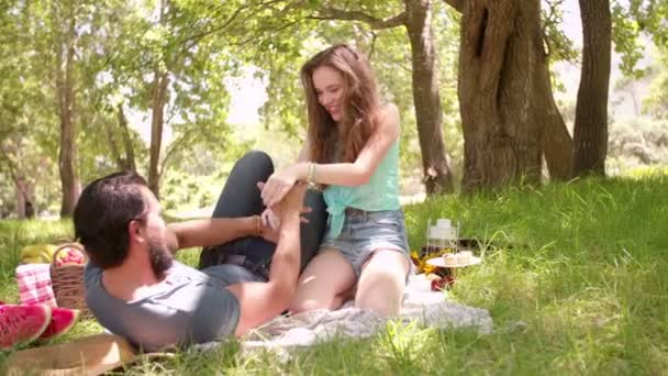 Playful couple laughing and tickling in park