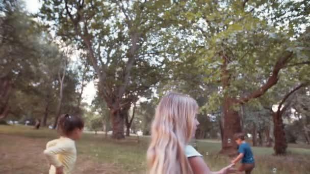 Děti běží a honí bubliny v parku