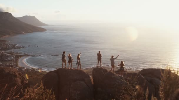 Siluety lidí tančí na skalách