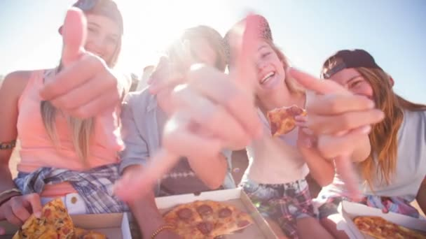Teen friends eating pizza outdoors