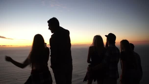 Teens looking at the ocean after sunset