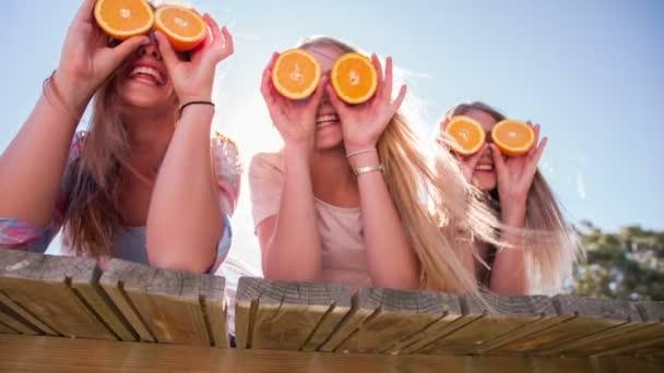 Dívka přátelé drží pomeranče pro oči