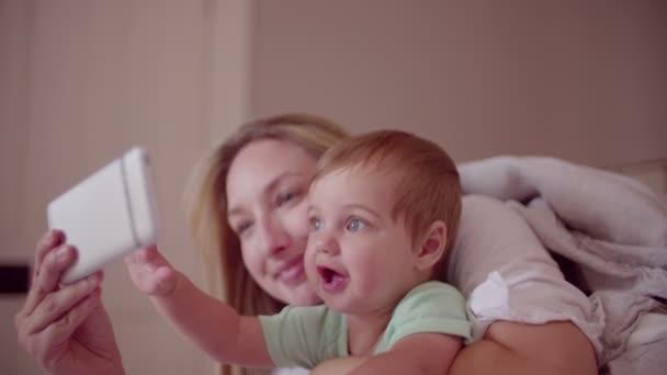 Sohn von Mutter und Baby mit smartphone