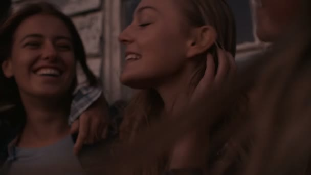 Dívka přátelé sedí v řadě během soumraku