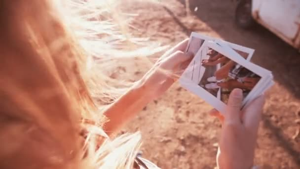 Girl looking at instant photos outdoors