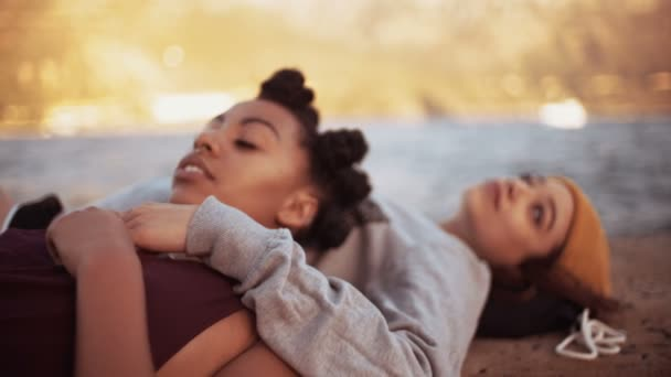 Teen girls lying on a harbor wall