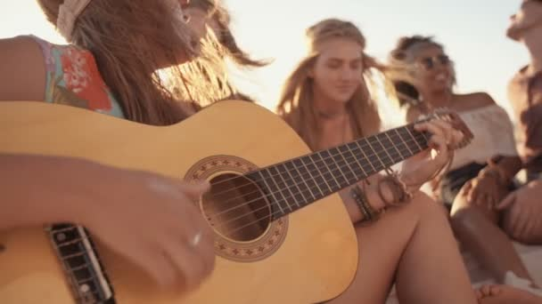 Girl playing guitar on the beach with friends