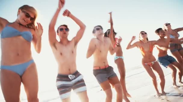 Group of friends jumping together at the beach