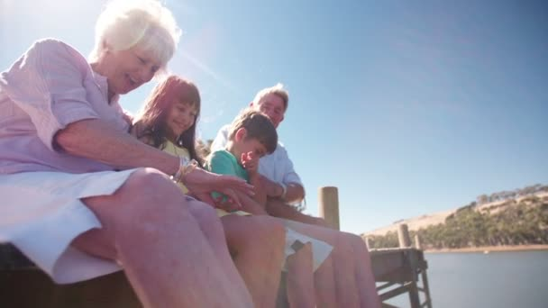 Grandchildren sitting with grandparents on a jetty