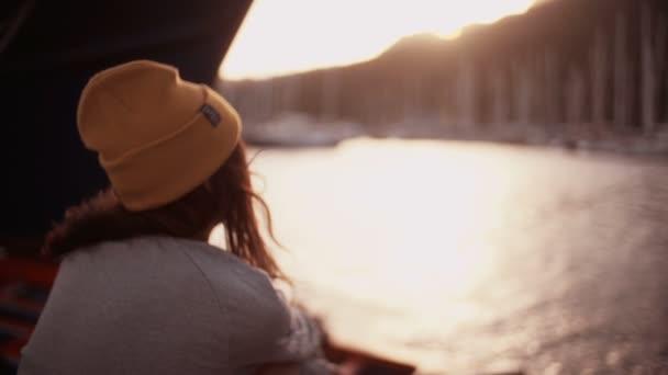Dospívající dívka sedí na lavici obžalovaných v přístavu