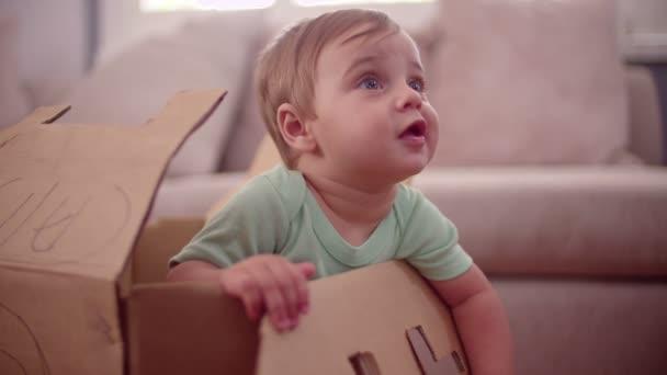 Baby boy playing in a cardboard box