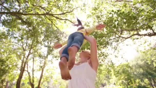 Mother spinning little girl in park