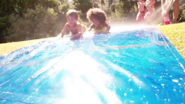 Girl and friends playing on a water slide