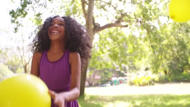 Afro girl catching balloons in park