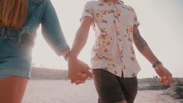 Hipster pár drží za ruce na pláži