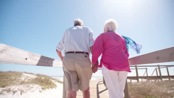 Starší pár spolu chodit na pláži