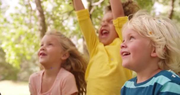 Děti hází konfety do vzduchu v parku