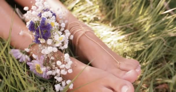 Dívčí chodidla v zelené trávě s květinami