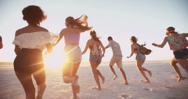 Mladí přátelé, chůzi na pláži při západu slunce