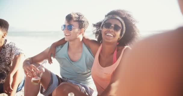 Mixed race couple drinking beer on the beach on a summer day