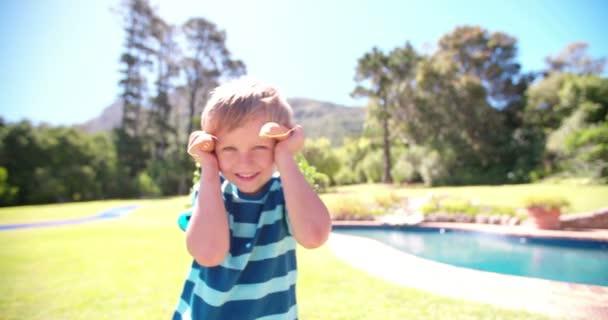 Kisfiú játékosan pózol a sárgarépát, a fülek