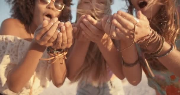 Girls blowing confetti from hands on beach