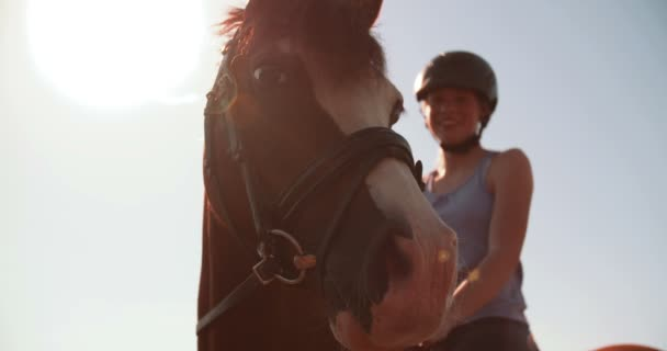 Teen girl with a helmet on riding her horse