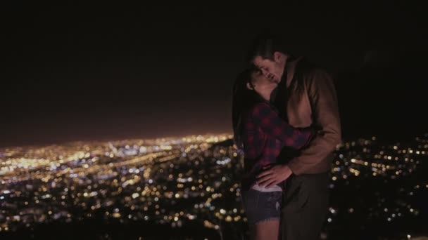 Couple kissing with city lights in the background