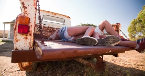 Legs of teen couple kissing in back of vintage truck