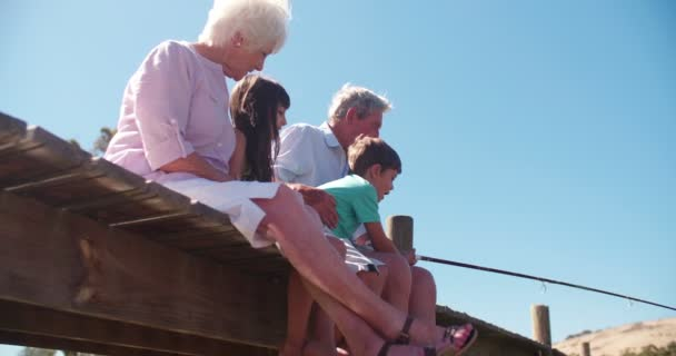 Prarodiče, sedí s vnoučaty na molo
