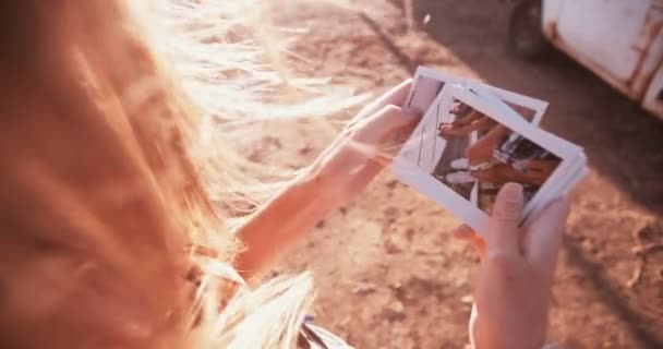 Teens looking at instant photos outdoors