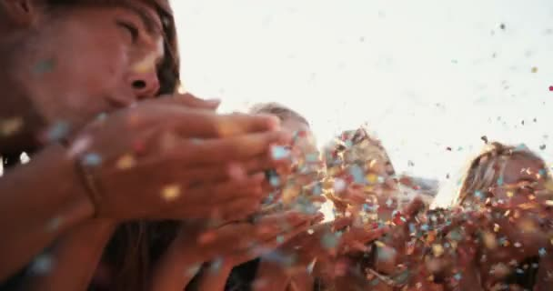 Teens blowing colorful confetti together