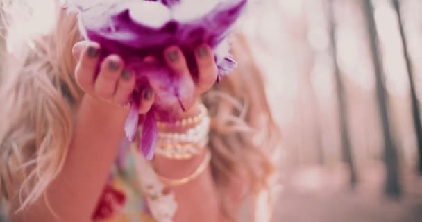 Boho girl blowing brightly coloured pink feathers