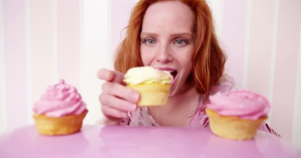woman is eating cupcakes
