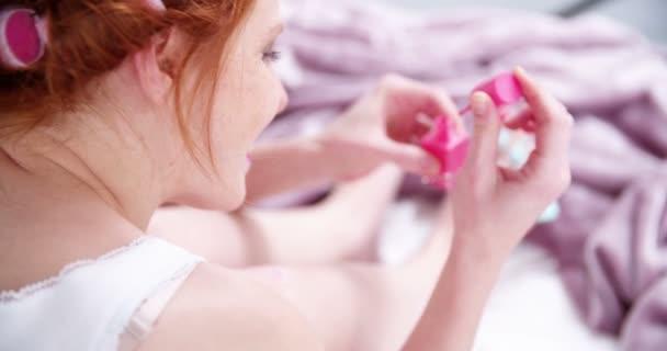 Dívka maluje její nehty růžový