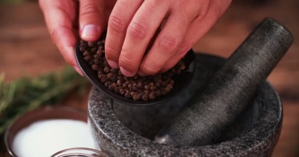 Black peppercorns being put into a mortar and pestle